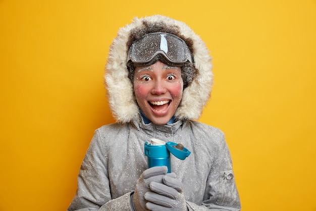 즐거운 활동적인 젊은 여성 관광객은 겨울에 스노 보드를 즐깁니다. 따뜻한 재킷을 입고 서리 음료로 덮인 장갑을 끼고 뜨거운 차에는 눈 덮인 휴식이 있습니다. 멋진 계절 리조트 레저 야외 활동