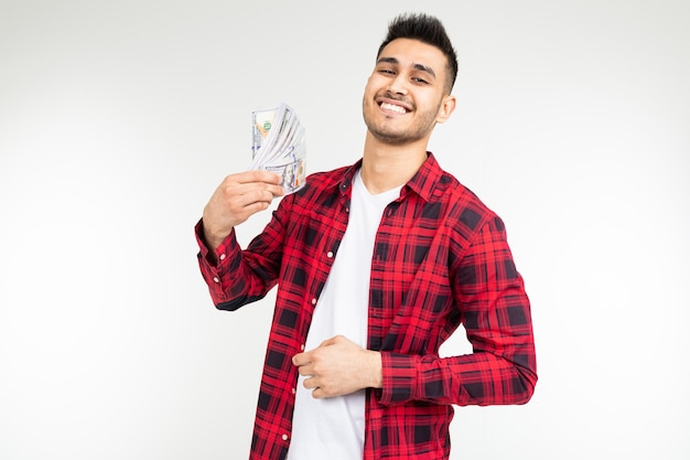 Joyful adorable brunette man won the lottery and received a cash prize on a white background with copy space.