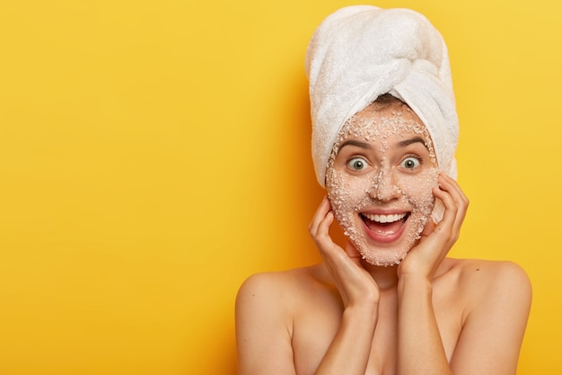 Joyful adorable woman with glad facial expression, applies natural sea salt mask, has healthy well cared skin, wears towel on head, enjoys hygienic treatments