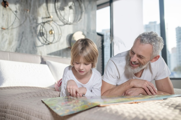 Joyful adult bearded dad with child lying on bed with book on weekend