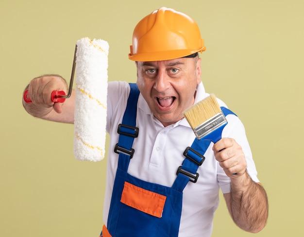 Радостный взрослый мужчина-строитель держит роликовую кисть и кисть, изолированные на оливково-зеленой стене