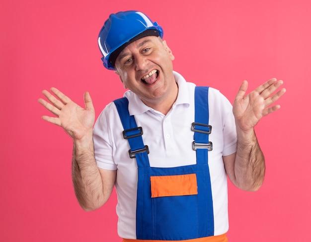 L'uomo caucasico adulto gioioso del costruttore in uniforme sta con le mani alzate sul colore rosa