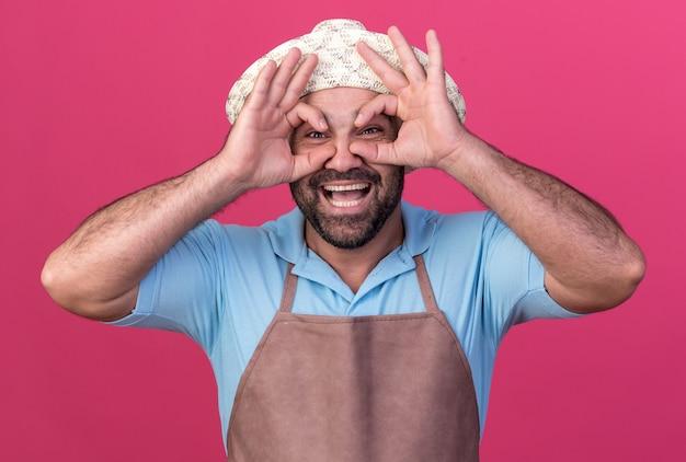 コピースペースとピンクの壁に分離された指を通してガーデニング帽子をかぶってうれしそうな大人の白人男性の庭師
