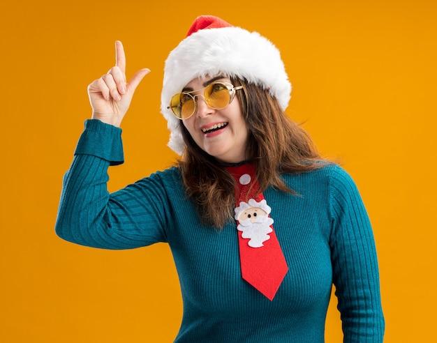 Gioiosa donna caucasica adulta in occhiali da sole con cappello santa e cravatta santa rivolta verso l'alto isolato su sfondo arancione con spazio di copia
