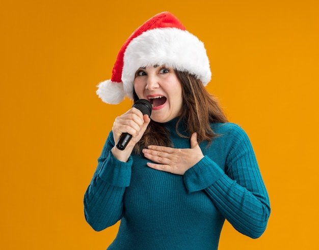 Joyful adult caucasian woman with santa hat holds mic and puts hand on chest isolated on orange background with copy space
