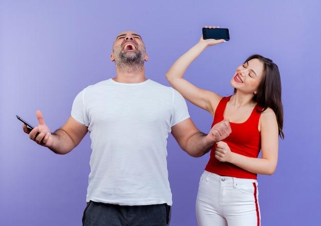 즐거운 성인 커플 모두 휴대 전화를 들고 닫힌 눈으로 예 제스처를하고