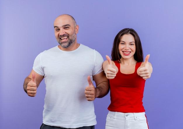 Gioiosa coppia adulta alla ricerca che mostra i pollici in su