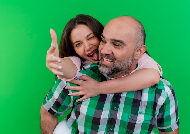 うれしそうな大人のカップルの男性は、彼の背中に女性を保持している側を見て、手を伸ばして舌を見せてウィンクしている女性