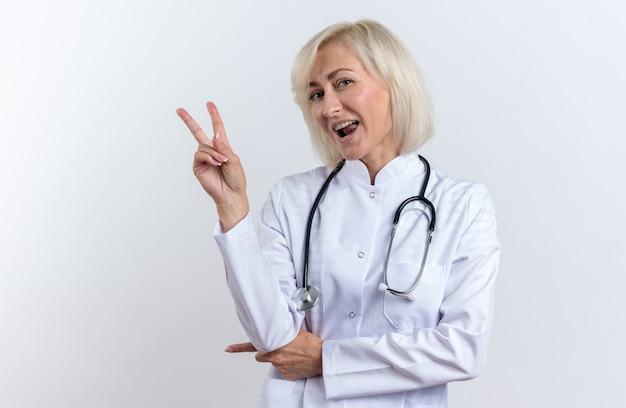 흰색 벽에 복사 공간이 격리된 청진기 몸짓 승리 기호가 있는 의료 가운을 입은 즐거운 성인 여성 의사