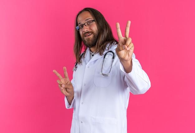 의료 가운과 청진기를 착용하고 프로필 보기에 안경을 쓰고 분홍색 벽에 격리된 카메라를 바라보는 평화 사인을 하는 즐거운 성인 남성 의사