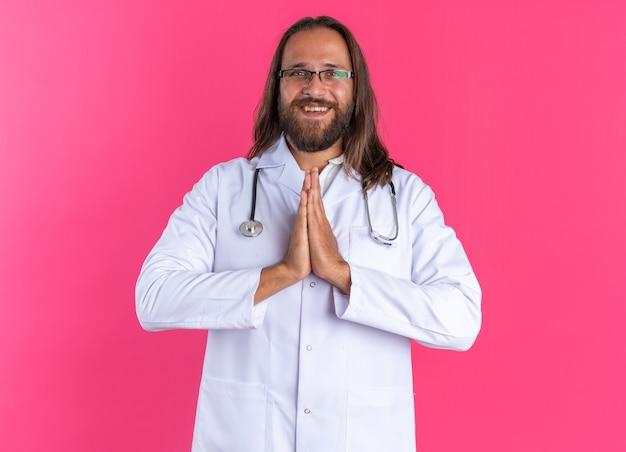 Gioioso medico maschio adulto che indossa una tunica medica e uno stetoscopio con gli occhiali che guarda la telecamera tenendo le mani insieme isolate sulla parete rosa