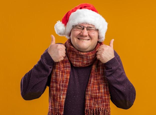 Gioioso uomo adulto con gli occhiali e il cappello della santa che morde il labbro che mostra i pollici in su con gli occhi chiusi isolati su sfondo arancione