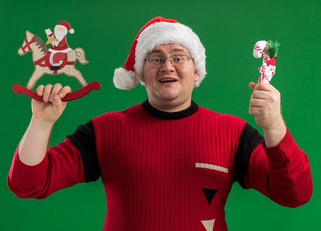 Joyful adult man wearing glasses and santa hat holding santa on rocking horse figurine and candy cane ornament looking at camera isolated on green background