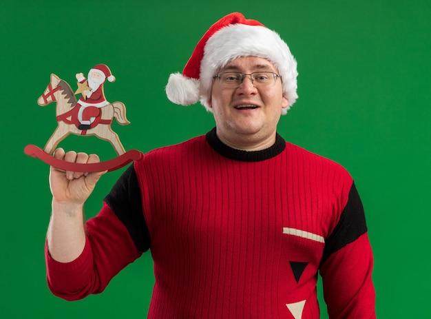 Joyful adult man wearing glasses and santa hat holding santa on rocking horse figurine isolated on green background