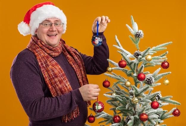 Gioioso uomo adulto con gli occhiali e cappello da babbo natale con la sciarpa intorno al collo in piedi in vista di profilo vicino all'albero di natale decorato con palline di natale guardando la telecamera isolata su sfondo arancione