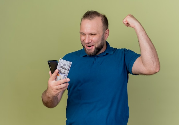 Joyful adult slavic man holding dollar and mobile phone looking at them and doing yes gesture