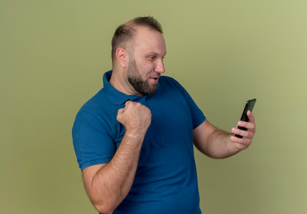 Joyful adult slavic man holding and looking at mobile phone doing yes gesture