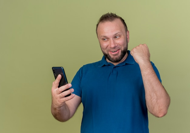 Joyful adult slavic man holding and looking at mobile phone and doing yes gesture