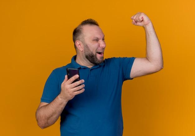 Радостный взрослый славянский мужчина держит мобильный телефон, глядя в сторону, делая жест да