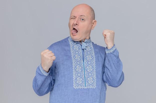 파란 셔츠를 입은 즐거운 성인 슬라브 남자가 혀를 내밀고 주먹을 쥐고 있다