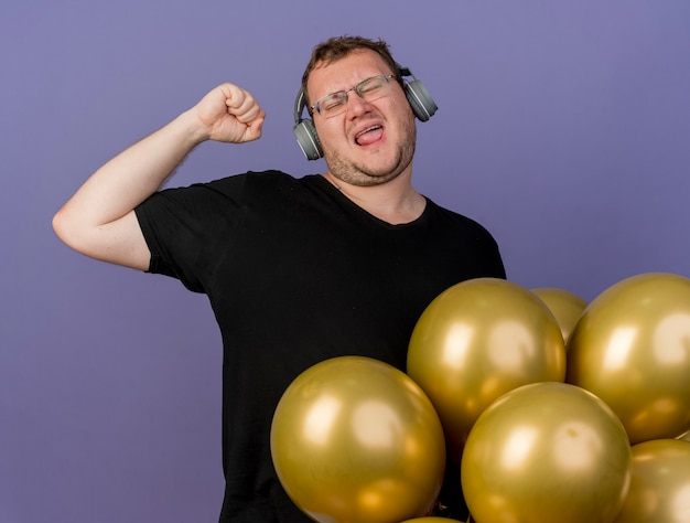 Joyful adult slavic man in optical glasses and on headphones stands with helium balloons raising fist up
