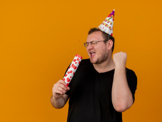 Joyful adult slavic man in optical glasses wearing birthday cap holds confetti cannon and keeps fist up