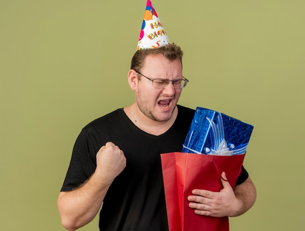 Joyful adult slavic man in optical glasses wearing birthday cap keeps fist and holds gift box in paper shopping bag