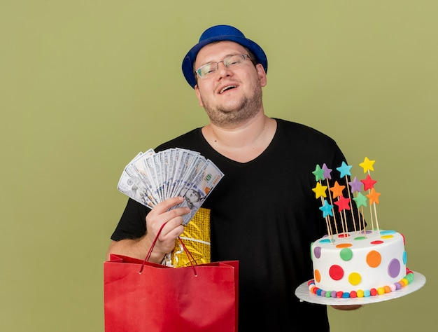 Joyful adult slavic man in optical glasses wearing blue party hat holds money gift box paper shopping bag and birthday cake
