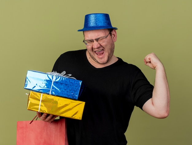 Joyful adult slavic man in optical glasses wearing blue party hat keeps fist holds gift boxes and paper shopping bag