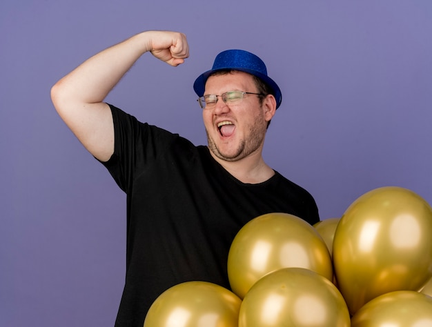 Joyful adult slavic man in optical glasses wearing blue party hat raises fist up standing with helium balloons