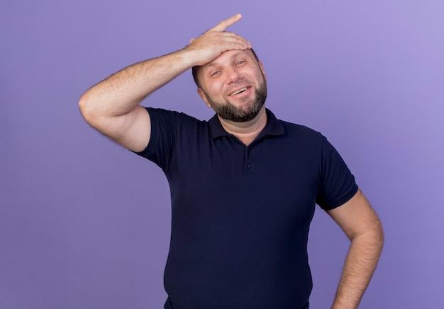 Радостный взрослый славянский мужчина положил руку на лоб, глядя изолированно