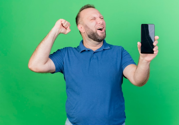 Joyful adult slavic man showing mobile phone and doing yes gesture with closed eyes isolated on green wall