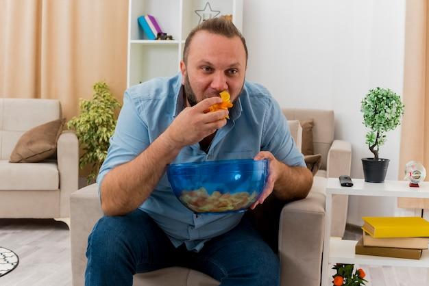 Gioioso uomo adulto slavo si siede sulla poltrona tenendo e mangiando una ciotola di patatine all'interno del soggiorno