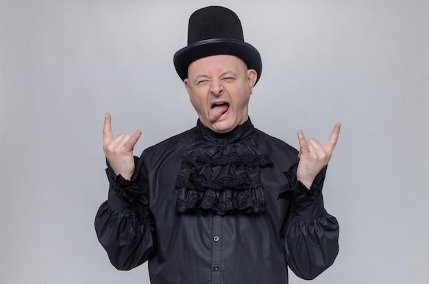 모자와 검은 고딕 셔츠를 입은 즐거운 성인 슬라브 남자가 혀를 내밀고 몸짓 뿔 기호