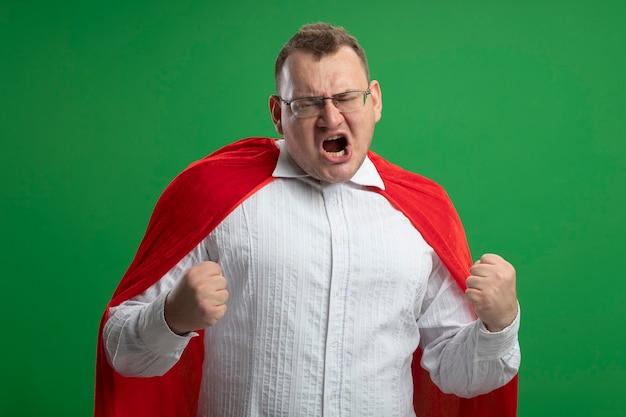 緑の壁に隔離されたはいジェスチャーをしている眼鏡をかけている赤いマントのうれしそうな大人のスラブのスーパーヒーローの男