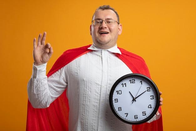 Радостный взрослый славянский супергерой в красной накидке в очках держит часы, делает хорошо, знак изолирован на оранжевой стене