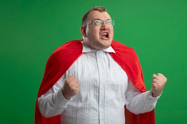 緑の壁に隔離されたはいジェスチャーをして見上げる眼鏡をかけている赤いマントのうれしそうな大人のスラブのスーパーヒーローの男
