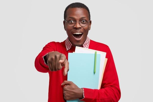 Радостный афроамериканский студент колледжа показывает указательными пальцами впереди, у него счастливое выражение лица, у него темная кожа, он одет в красный свитер