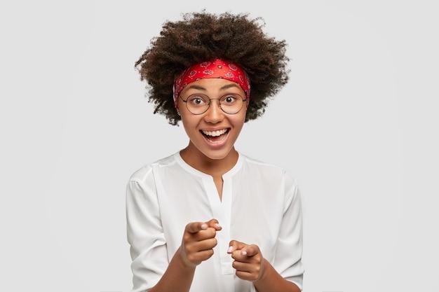 Радостная афроамериканка показывает обоими указательными пальцами, выражает свой выбор, у нее вьющиеся волосы и темная кожа, она носит круглые очки и повседневную рубашку, изолирована на белой стене