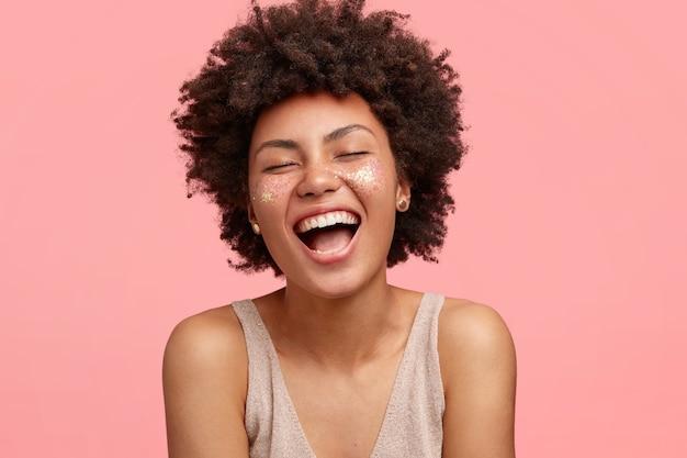 肌が黒く、楽しく笑い、口を大きく開き、頬に輝き、目を閉じ、巻き毛があり、ピンクの壁に孤立している、うれしそうなアフリカ系アメリカ人の女性。人と幸福の概念