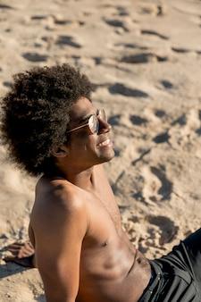 Joyful african american male sitting on sand in sunlight