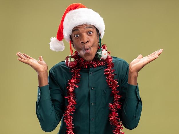 Gioioso uomo afroamericano in santa cappello con ghirlanda e palle di natale sulle orecchie divertendosi guardando la telecamera in piedi su sfondo verde