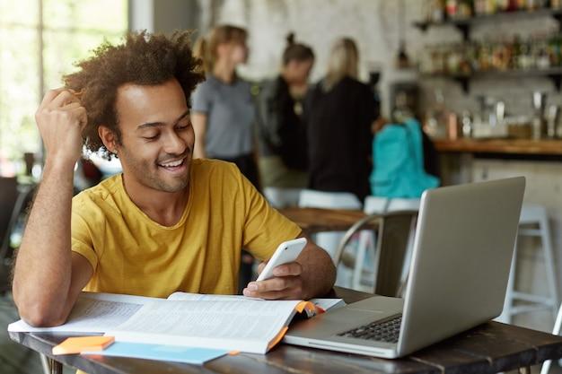 Радостный афро-американский студент сидит за деревянным столом в кафе в окружении книг, тетрадей, ноутбука, держа в руке сотовый телефон и смотрит с удовольствием