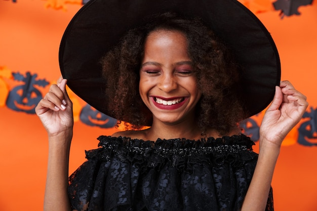 Joyful african american woman in black halloween costume laughing with eyes closed isolated over orange pumpkin wall