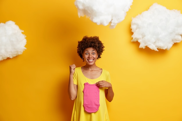 Joyful african american woman clenches fist and feels happy as finds out she will have daughter, holds baby singlet over tummy, stands against yellow  with clouds above. pregnancy concept
