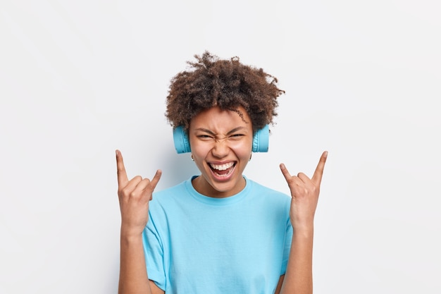 Joyful african american woman enjoys rock music makes heavy metal gesture smiles broadly uses stereo headphones dressed in basic blue t shirt isolated over white wall feels wild and free