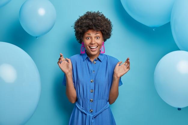 Gioiosa donna afroamericana felice di incontrare gli amici alla festa, sta con le mani alzate sorride ampiamente, festeggia il compleanno, indossa un vestito blu, non vede l'ora di aprire i regali, ha molte mongolfiere intorno