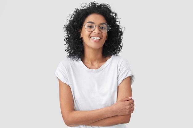 うれしそうなアフリカ系アメリカ人の女性は、手を組んで、良い冗談を笑い、カジュアルな服と丸い眼鏡をかけ、孤立しています。黒い肌の幸せな若い女性が屋内でポーズをとる