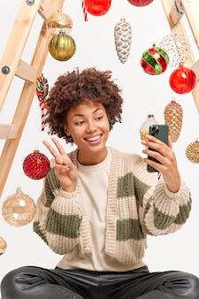 うれしそうなアフリカ系アメリカ人の女性が自分撮りを撮る平和のジェスチャーが携帯電話を保持するカジュアルなジャンパーを着て幸せな気分のポーズをとる