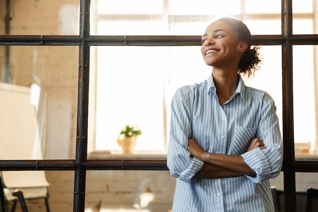 Joyful african american woman with hands crossed smiling while leaning on glass wall in modern office